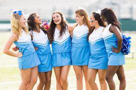 Team of excited cheerleaders performing at football game