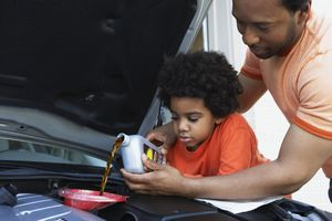 Father and son adding oil to car engine