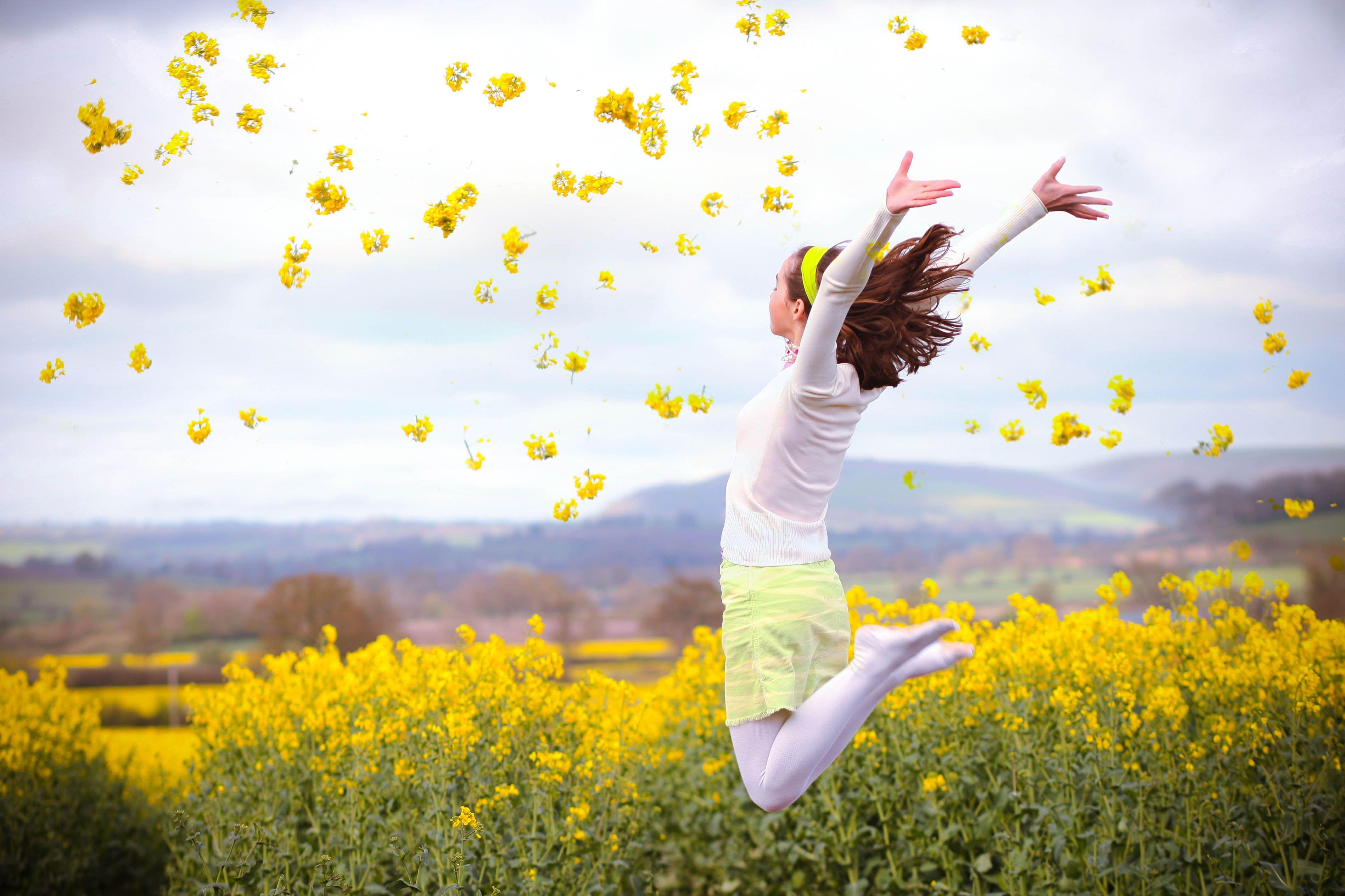 Girl jumping in yellow Rapeseed field