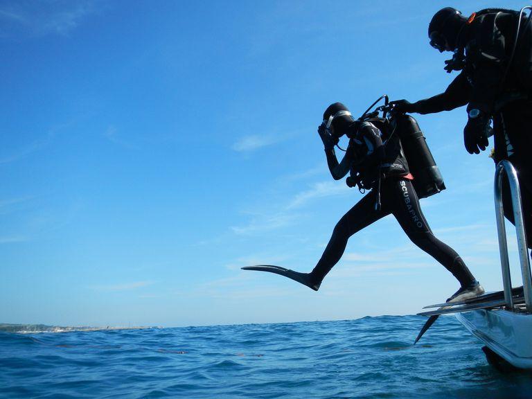 Scuba diver in wetsuit and full gear stepping into the water from a boat.