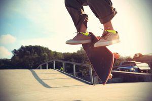 skateboarder legs doing a trick heelflip at skatepark