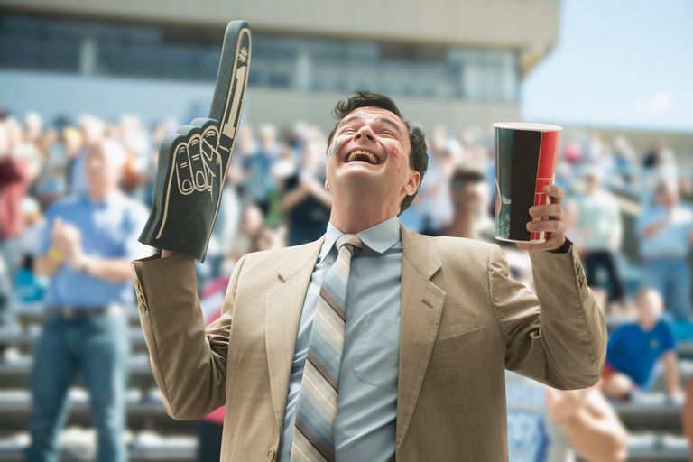 Happy businessman sports fan with foam hand and drink
