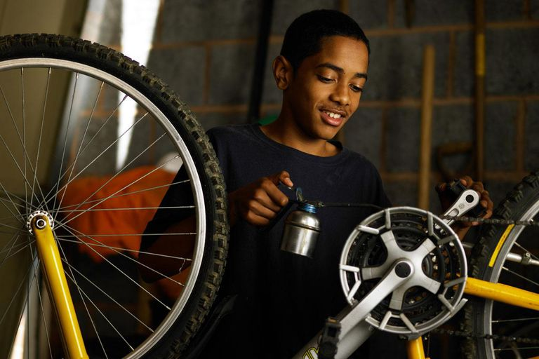 Teenager oiling bicycle chain
