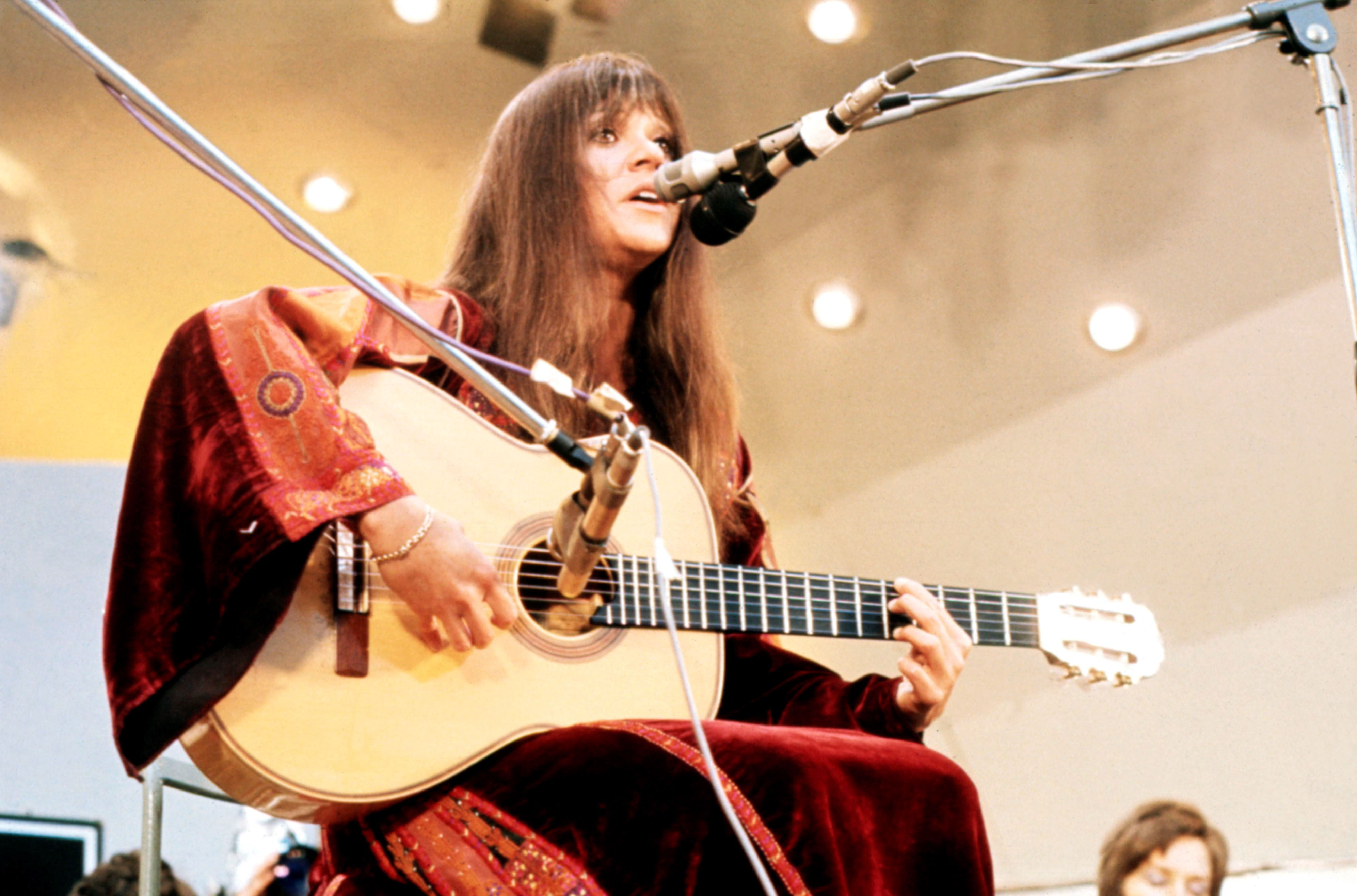 Melanie playing acoustic guitar and singing