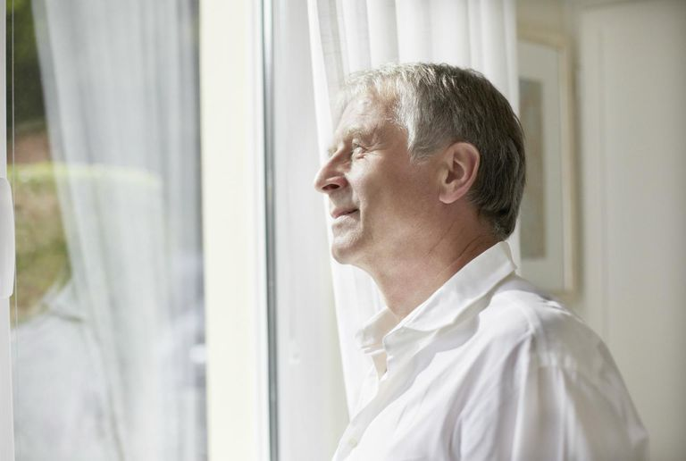Smiling mature man looking out of window