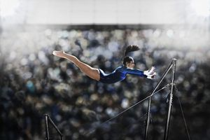 A Female Gymnast, a Young Woman Performing on the Parallel Bars, in Mid Flight Reaching Towards the Top Bar