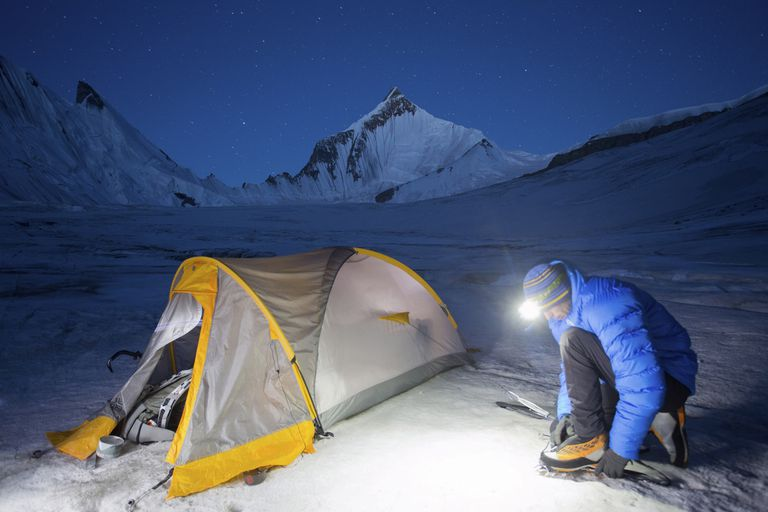 A climber straps on crampons in the early morning hours to get an alpine start in the Himalayas.