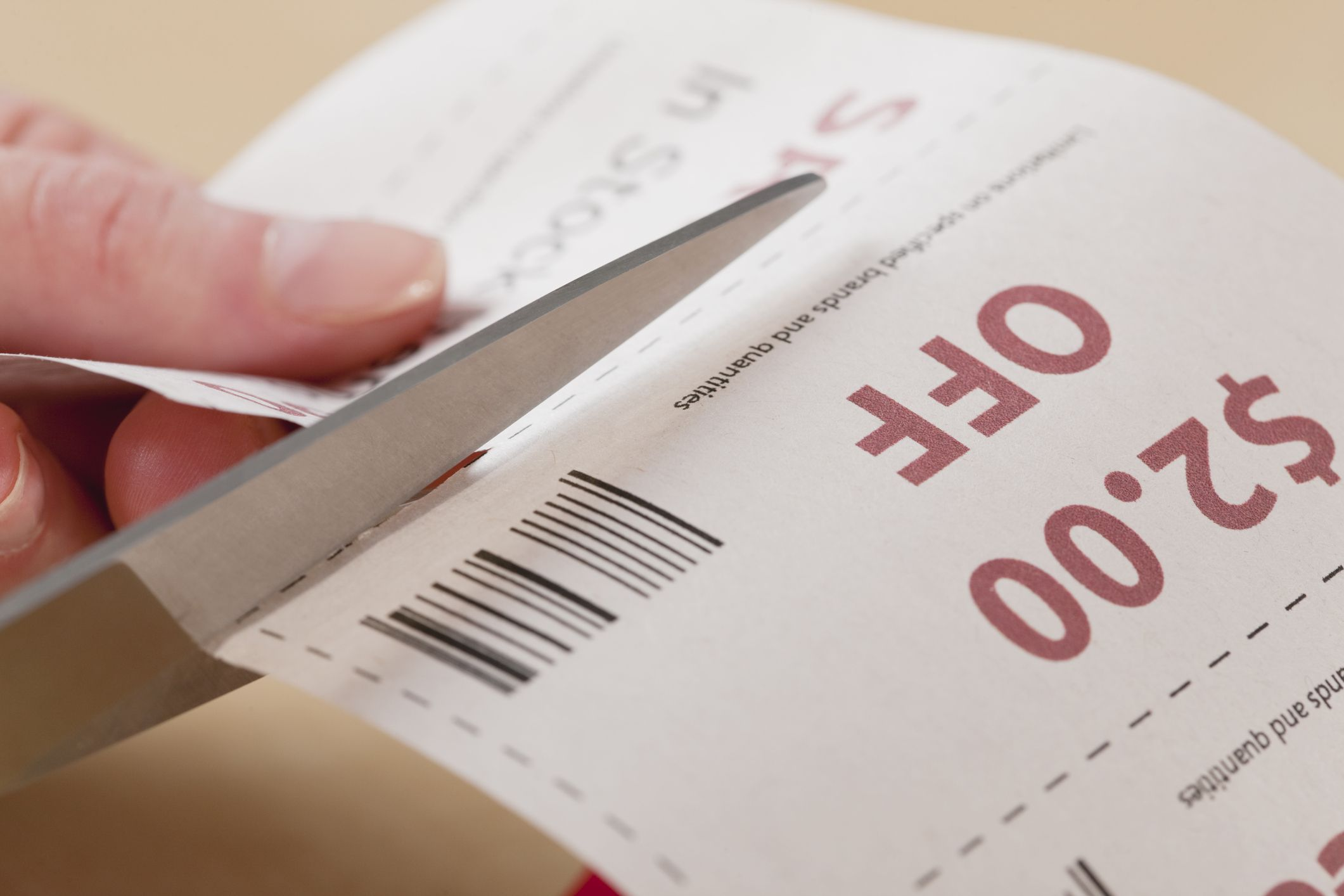 person cutting coupons