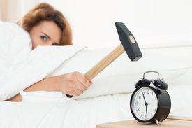 Woman hitting alarm clock with hammer