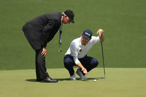 Louis Oosthuizen of South Africa talks with a rules official on the 10th green during the first round of the Masters at Augusta National Golf Club on April 11, 2019 in Augusta, Georgia