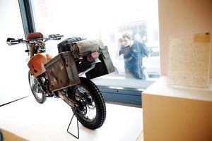 A man looks through a window at a Honda motorcycle.