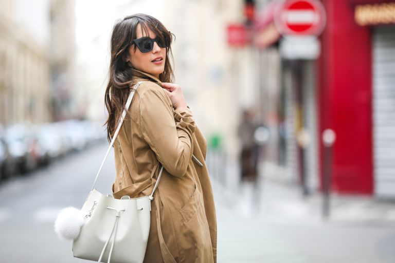 Woman in trench coat and white purse - street style