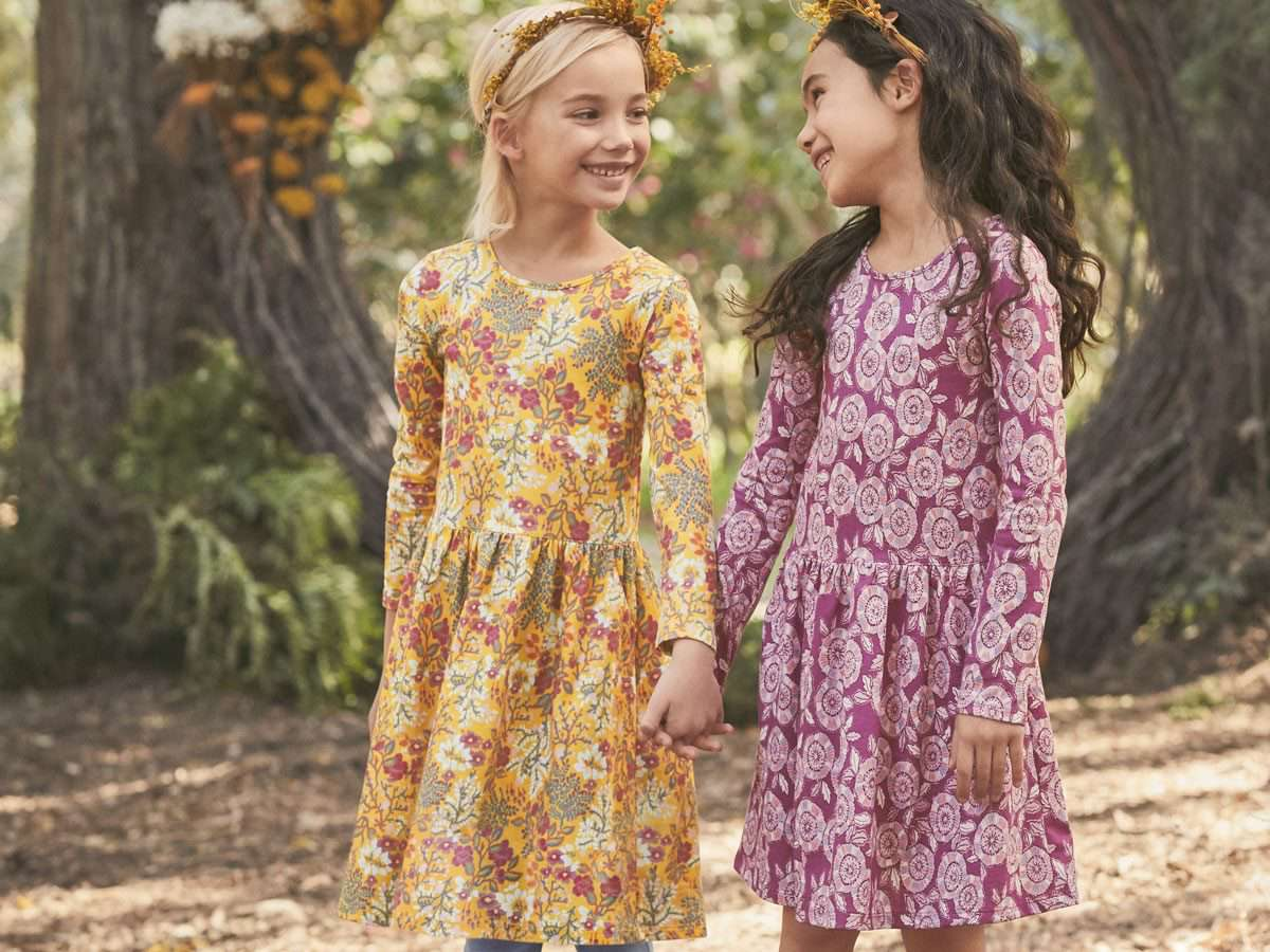 Two girls standing in the woods wearing dresses and flower crowns