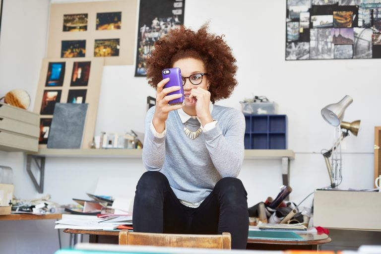 Woman wearing skinny jeans at office using smartphone