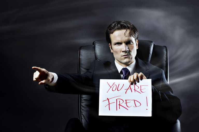 """man holding """"you are fired"""" sign and pointing"""