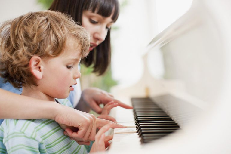 Woman teaching boy to play piano