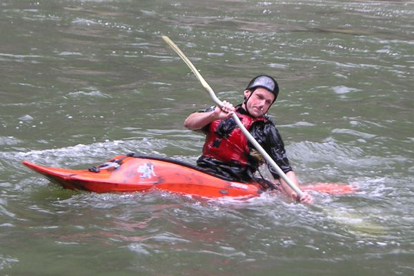 A kayaker paddles in a moving current