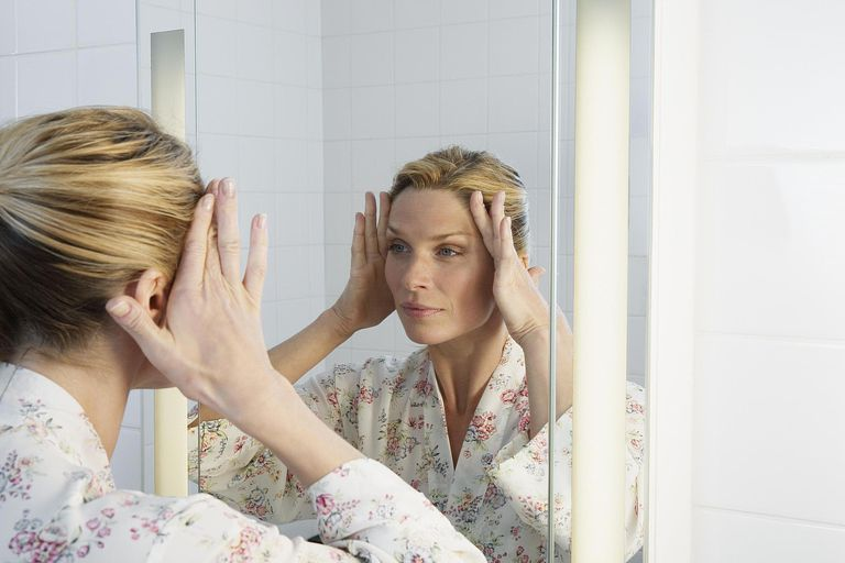 Woman smoothing out wrinkles on face with hands
