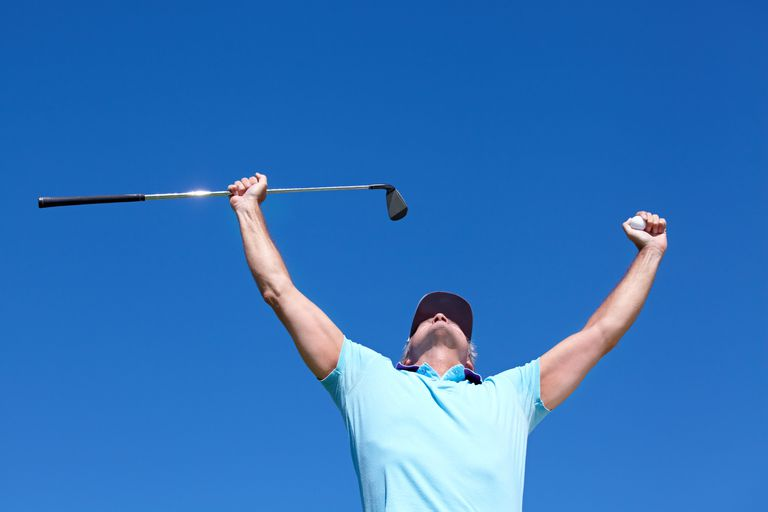 A golfer celebrates holing out