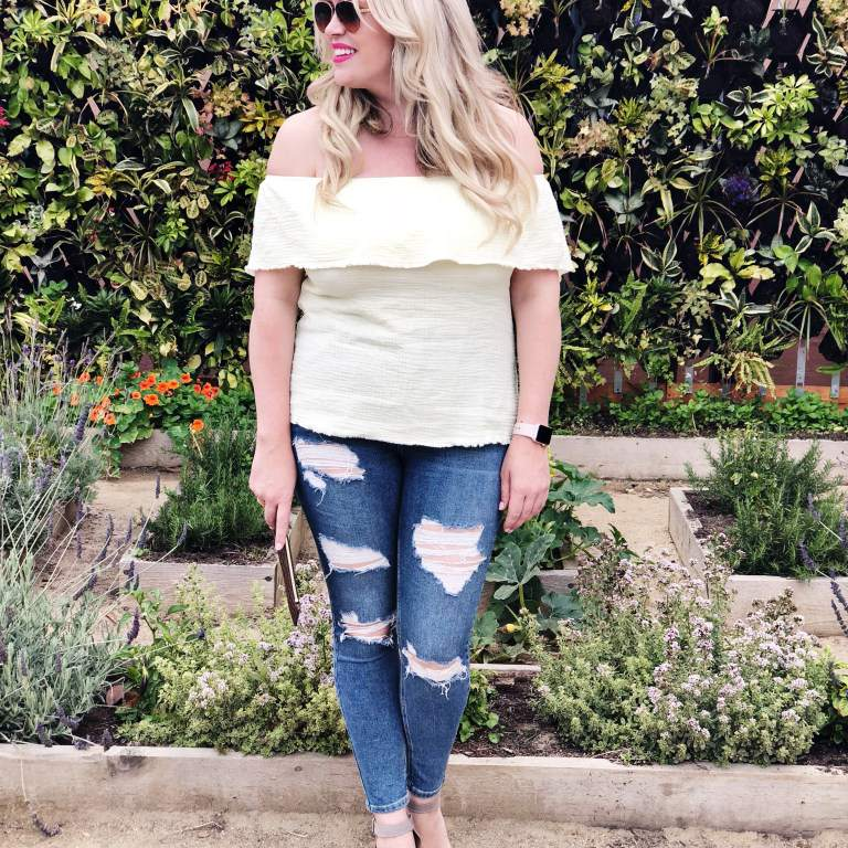 Woman in cold shoulder top and ripped jeans