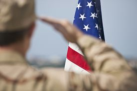 Soldier saluting the American flag after enlisting in the military.