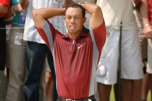 Tiger Woods appears disappointed after a mishit shot