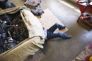 man under car doing repairs
