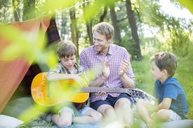Man and sons singing and clapping with guitar.