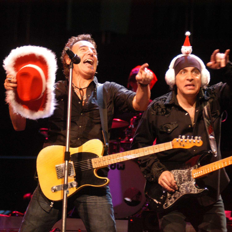 Bruce Springsteen and Steven Van Zandt performing, wearing christmas hats