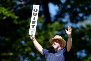 A marshal signals prior to a tee shot at a pro golf tournament