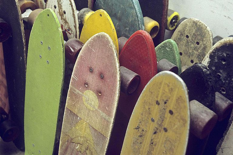 Rows of used skateboards leaning against a wall