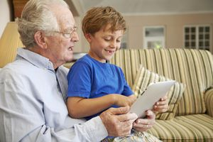 A grandfather and his grandchild on a tablet together