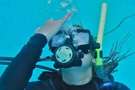 A scuba diver exhales to remove water from her scuba mask.