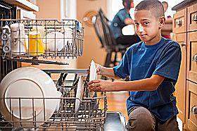 A young boy loading the dishwasher.