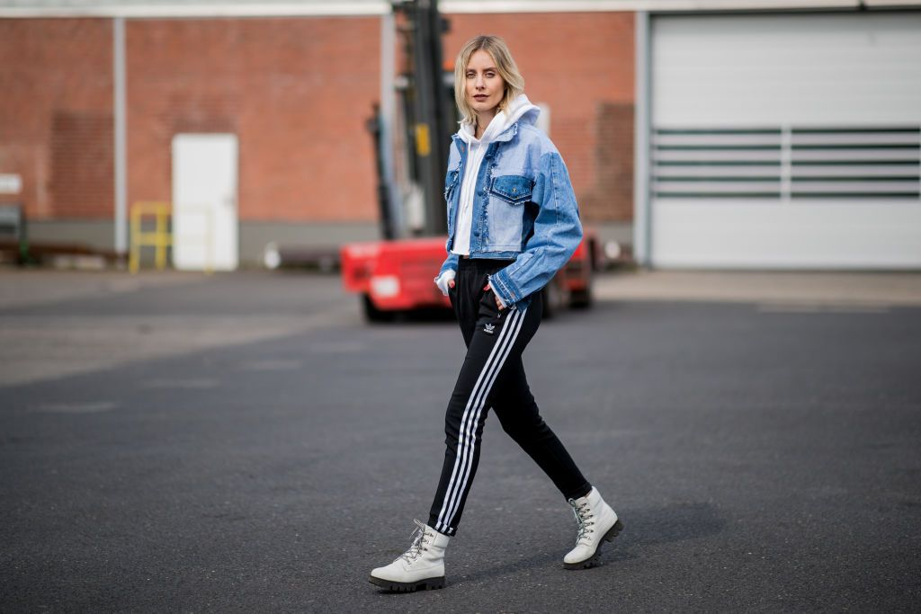 Woman wearing a jean jacket and track pants