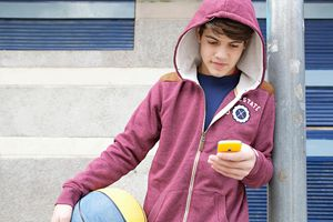 Teenager using smartphone in basketball court