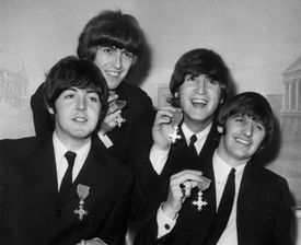 The Beatles Holding Medals