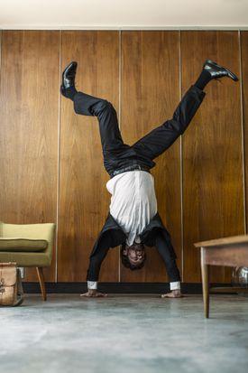 Caucasian businessman doing handstand