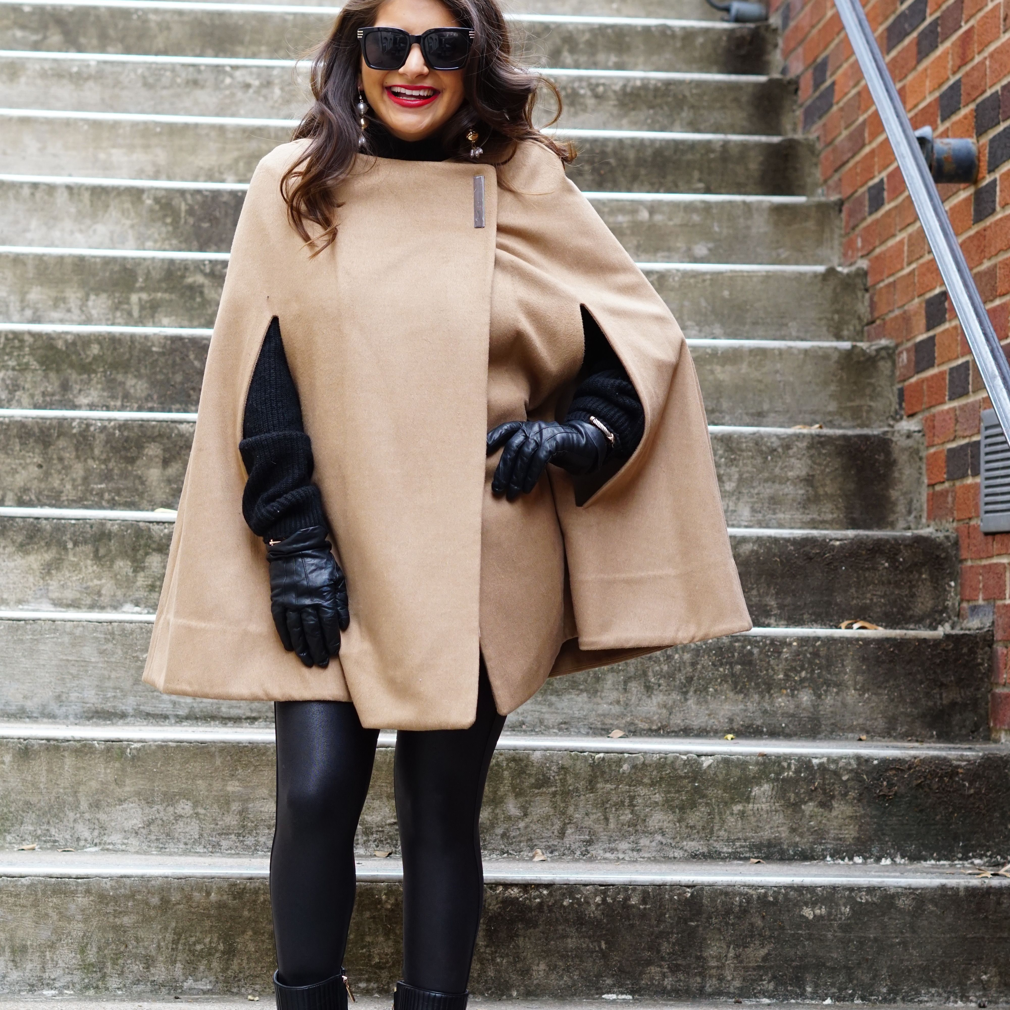Woman in camel cape coat and black leggings