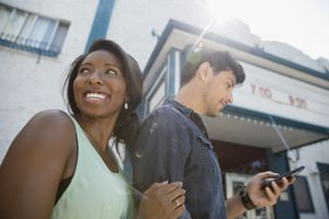 Smiling couple outside sunny movie theater