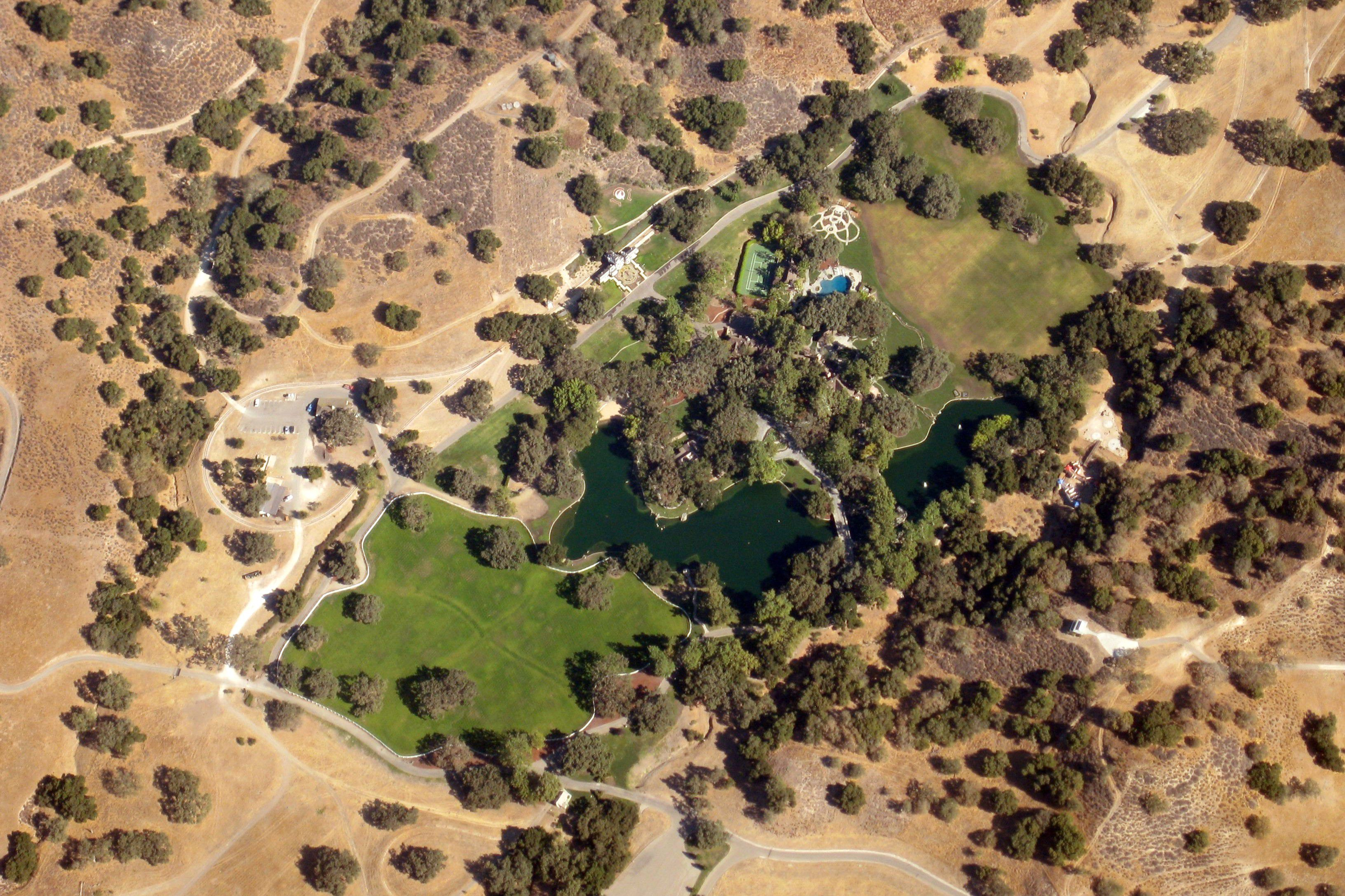 A distant aerial view of Neverland Ranch reveals a lush, green oasis surrounded by sere brown desert
