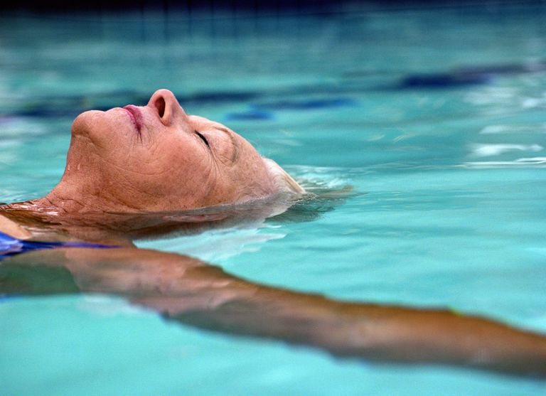 Senior woman floating in pool, eyes closed, side view