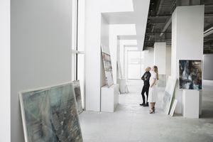 Art dealers examining paintings in a gallery.