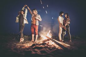 Two happy couples dancing at night party by the campfire.