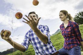 man juggling apples next to woman