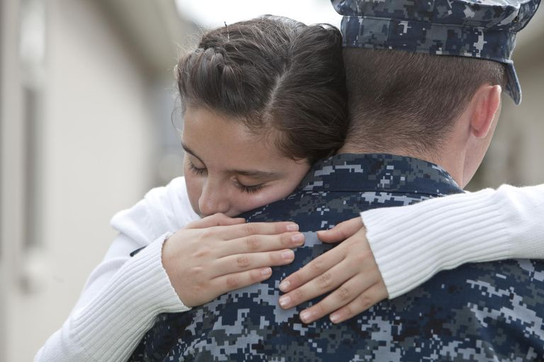 Girl hugging military did