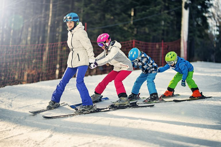 Kids practicing skiing with ski school instructor