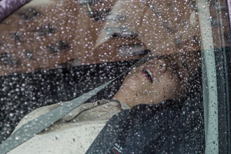 Woman sleeping in car with rain on the window