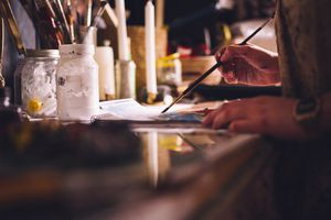 Artist painting on paper with a fine paintbrush