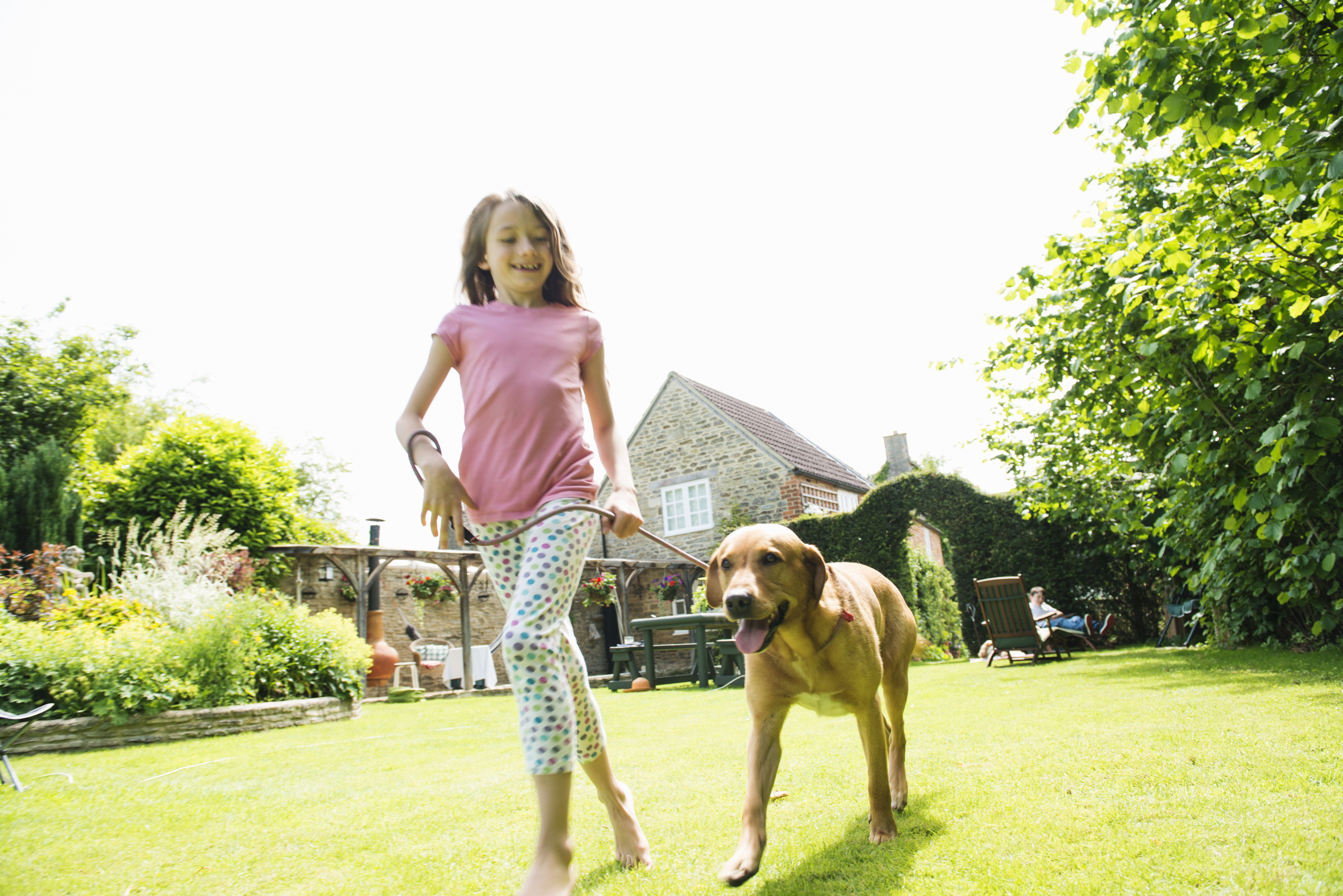 Girl walking dog on leash in garden as a part-time job.